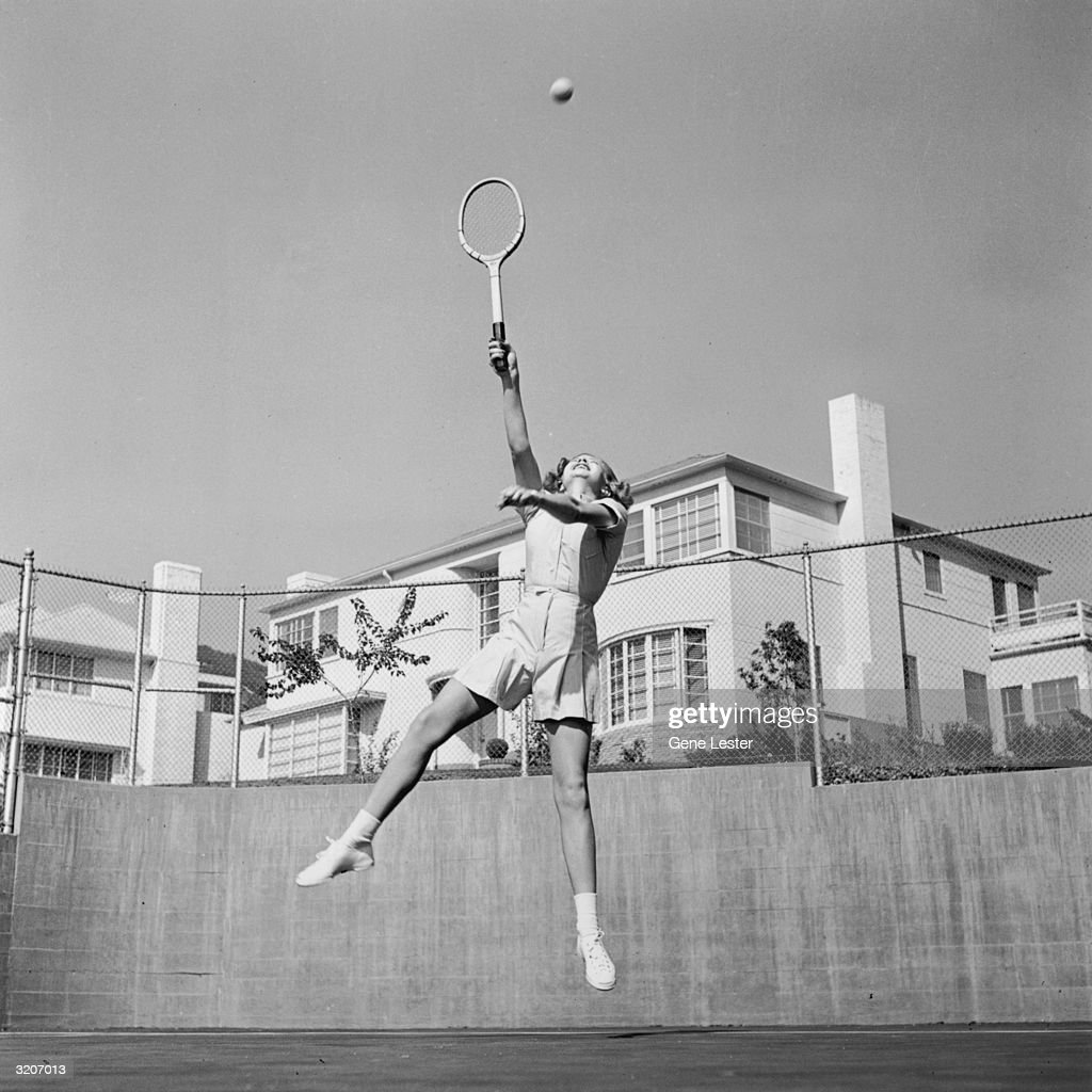 American actor Lana Turner leaps with her racket up, attempting to return a shot while playing tennis on a fenced court at her Sunset Plaza apartment complex, Los Angeles, California.