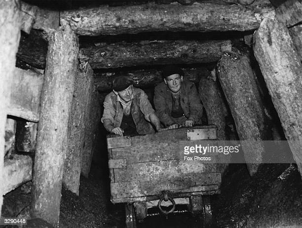 Miners bringing out a small truck of coal from the timbered workings
