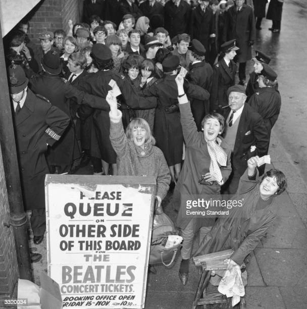 Fans of British pop group The Beatles jubilantly hold up their tickets for a Beatles concert beside a group of fans being restrained by police who...