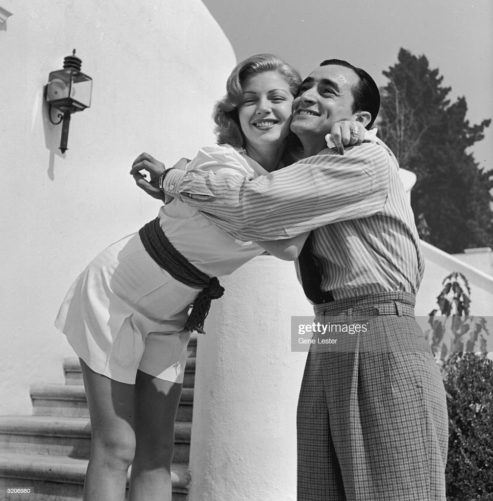 American actor Lana Turner smiles as she hugs Jimmy Sarno of the MGM Studios publicity department at her Sunset Plaza apartment complex, Los Angeles, California.