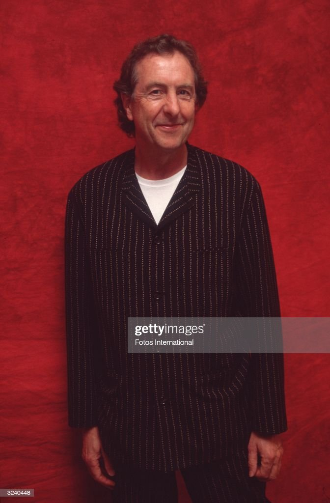 British actor, director, producer, composer and writer Eric Idle standing in front of a red background, Beverly Hills, California.