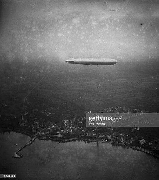 The Graf Zeppelin LZ 127 airship designed by the German airship pioneer Count Ferdinand von Zeppelin on its first trial flight over Friedrichshafen
