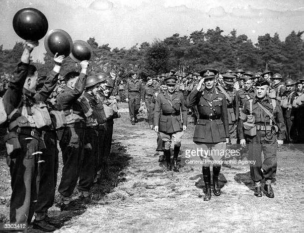 King George VI inspecting Canadian 3rd Division troops in Southern England some of whom are waving their helmets