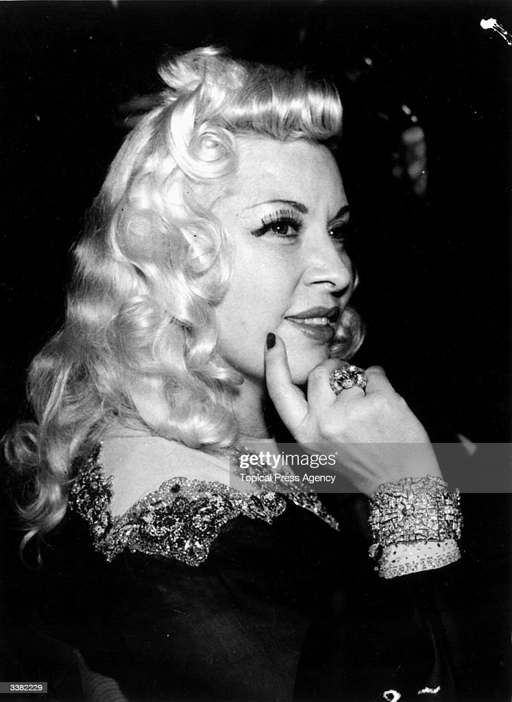American film icon and sex symbol Mae West (1892 - 1980) attends a reception at the Savoy Hotel during a visit to London, wearing some of her famous jewels.