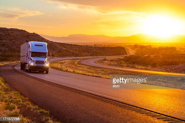 18-wheeler tractor-trailer truck on interstate highway at sunset