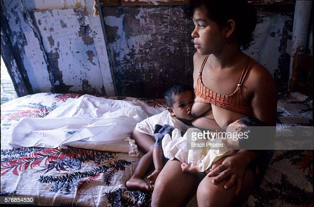 18years old mother breastfeeds her two babies in a favela hut teenage pregnancy associated with social issues lower educational levels and higher...