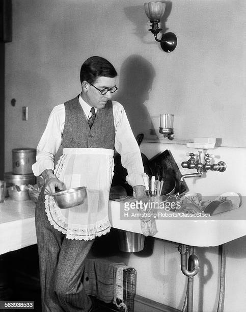1920s MAN IN APRON LEANING...