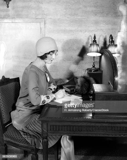 1920s WOMAN SITTING AT...