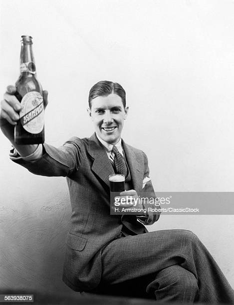 1930s MAN HOLDING UP HUGE...