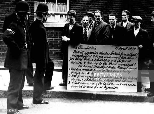 A group of men from the National Unemployed Workers Movement in Downing Street London with a 'protest postcard' listing various grievances and...