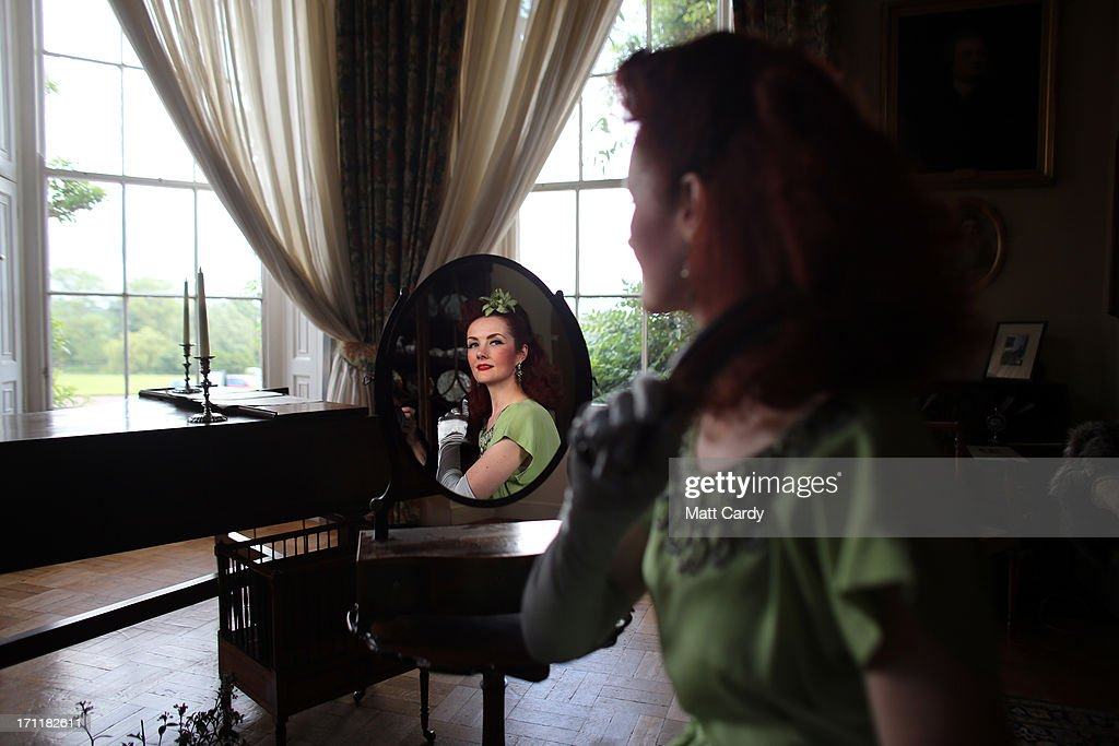1940s singer Lola Lamour poses for a photograph in the music room at Killerton House prior to her performance in the gardens on June 22, 2013 in Exeter, England. The National Trust property, near Exeter, is holding a two day vintage weekend with stalls selling vintage fashion, home ware and crafts, displays of classic cars and features an evening of entertainment which includes burlesque dancers.