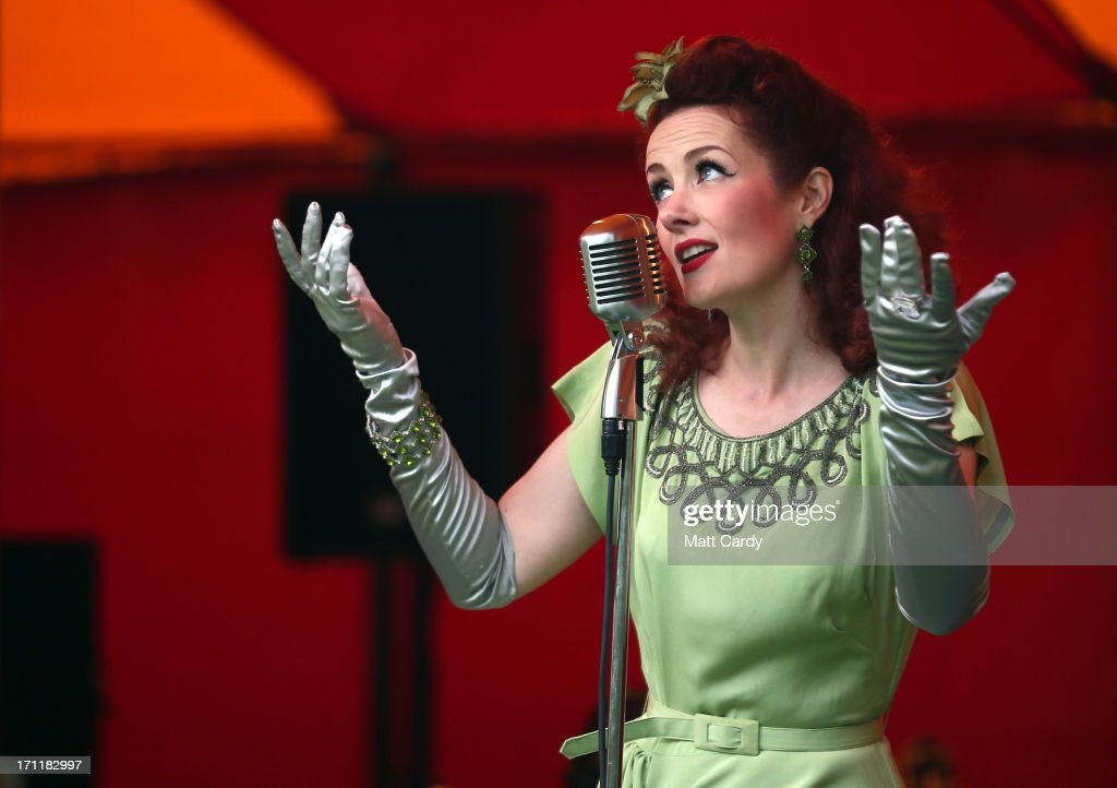 1940s singer Lola Lamour sings in a marque erected in the gardens at Killerton House on June 22, 2013 in Exeter, England. The National Trust property, near Exeter, is holding a two day vintage weekend with stalls selling vintage fashion, home ware and crafts, displays of classic cars and features an evening of entertainment which includes burlesque dancers.