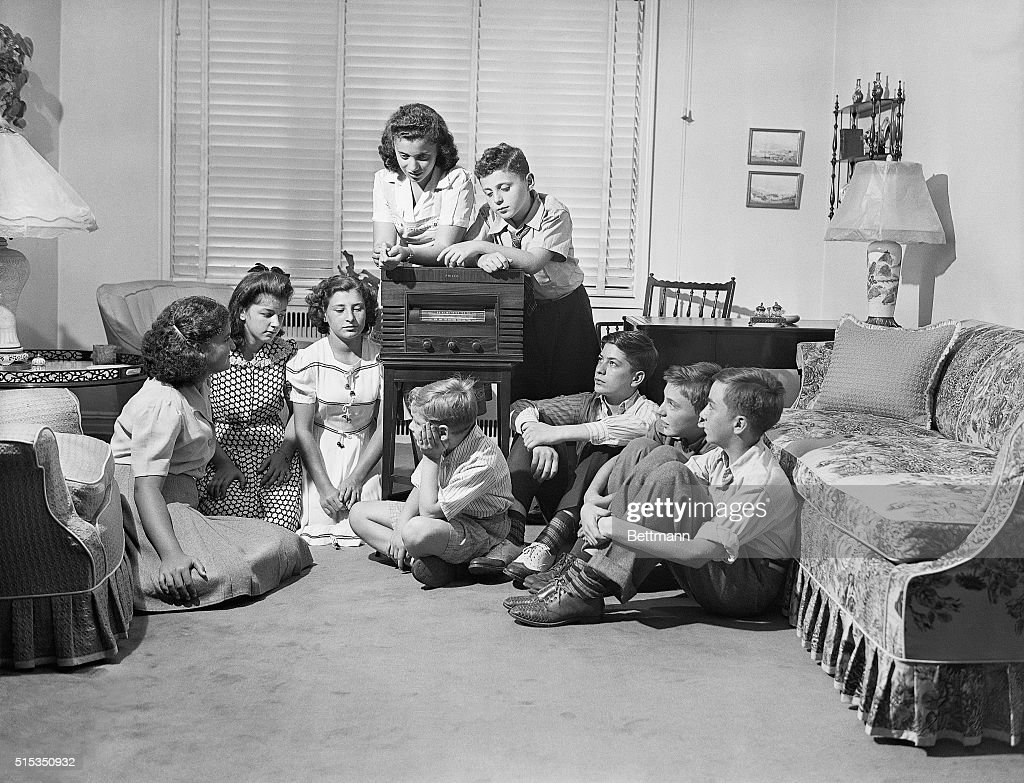 Betty Jean and Henry Schwaber, 13 and 10 respectively, are shown surrounded by their friends at their Jamaica, Long Island home listening to President Roosevelt's message to the youth of the world. It was on the suggestion of the Schwabers, offered in their letter to the White House, that the President timed his address so that the children of the Nation could hear it and share in this moment in history.