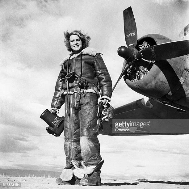 1943Margaret BourkeWhite at the ready standing by airplane propeller and fully garbed in leather fleece lined flight suit camera in hand 1943