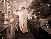 1950Nicky Hilton is shown in a kitchen with chef Walter Luth