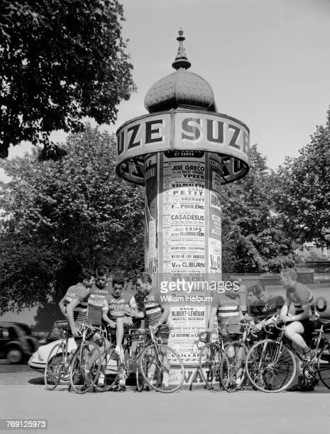 A bicycle racing team pauses around a Parisian kiosk Black and white