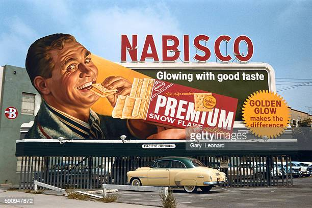 1950's billboard of manically happy and glowing man with red saltine box and old car beneath billboard
