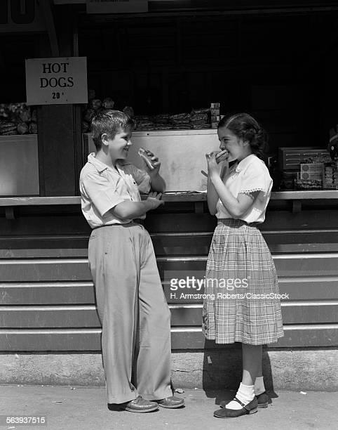 1950s BOY GIRL EATING HOT...
