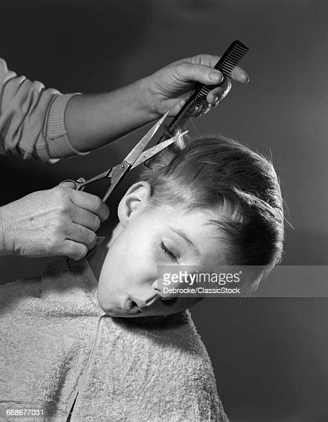 1950s BOY MAKING FACE AS...