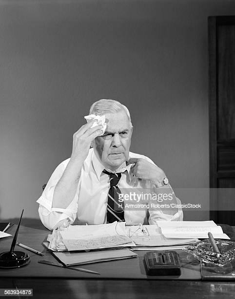 1950s BUSINESSMAN SITTING...
