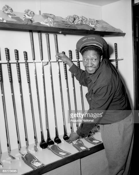 Caddie Master John Henry 'Leven' Williams adjusts the display of clubs during the 1950s Masters Tournament at Augusta National Golf Club in April of...