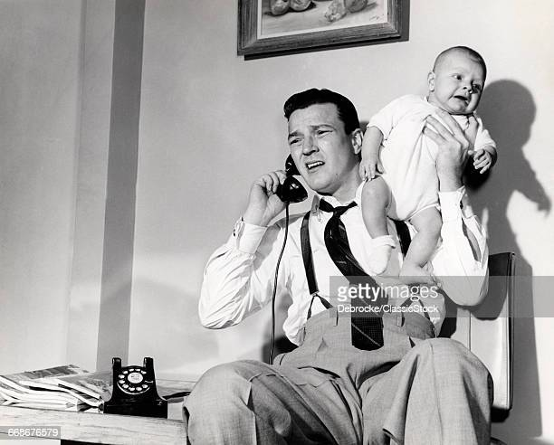 1950s FATHER HOLDING BABY...