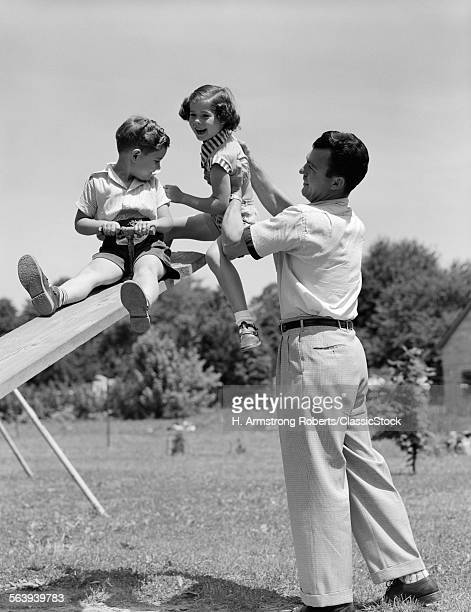 1950s FATHER LIFTING SON...