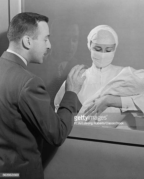 1950s FEMALE NURSE HOLDING...