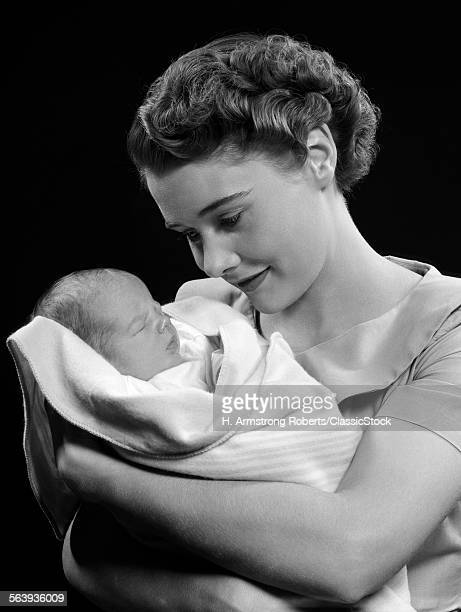 1950s MOTHER HOLDING BABY...