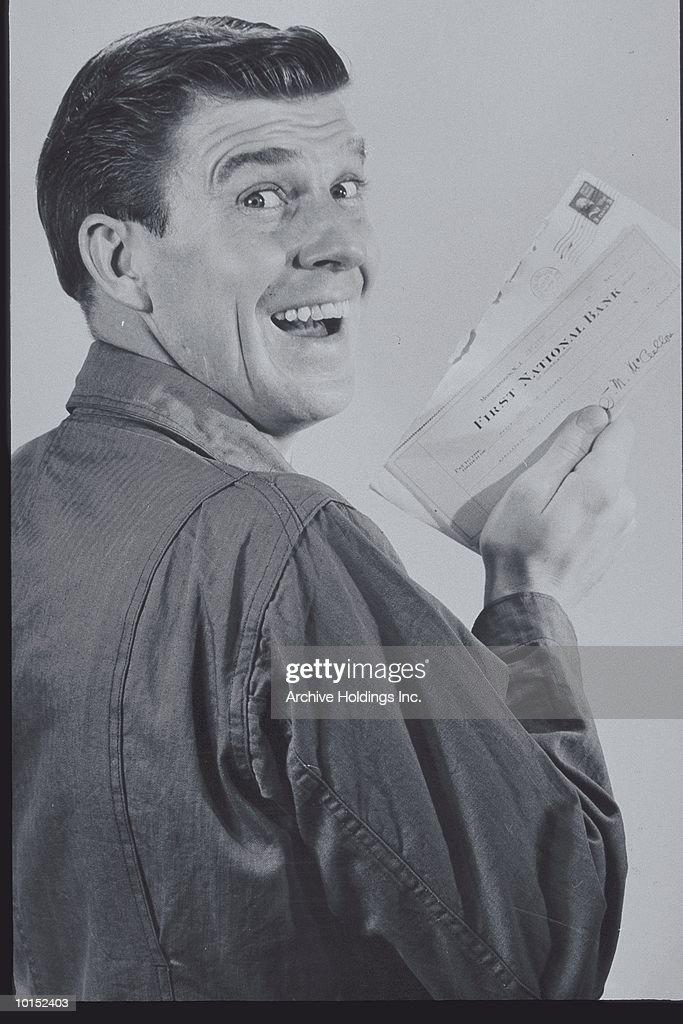 SMILING MAN HOLDING UP A CHECK, CIRCA 1950s : Stockfoto