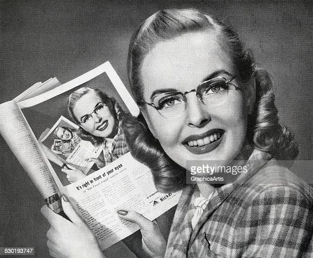 1950s woman holding a magazine with an optical illusion of repeating pictures of herself 1950