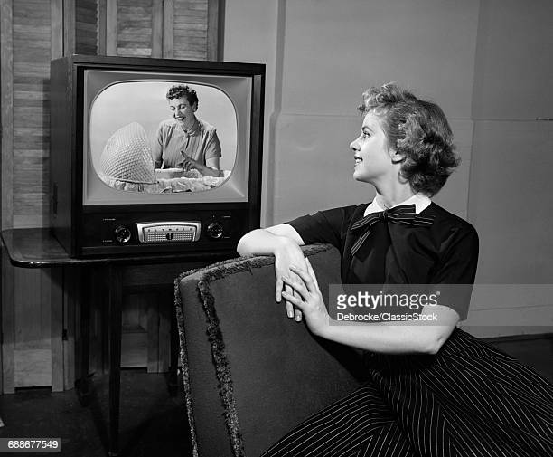 1950s WOMAN SITTING IN...