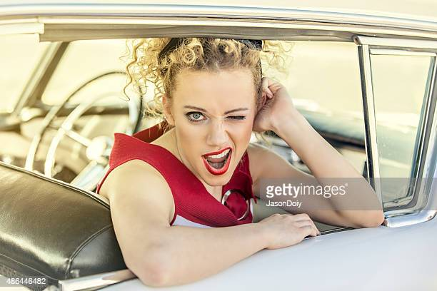 1950s Woman Winking at the Camera in a Vintage Car