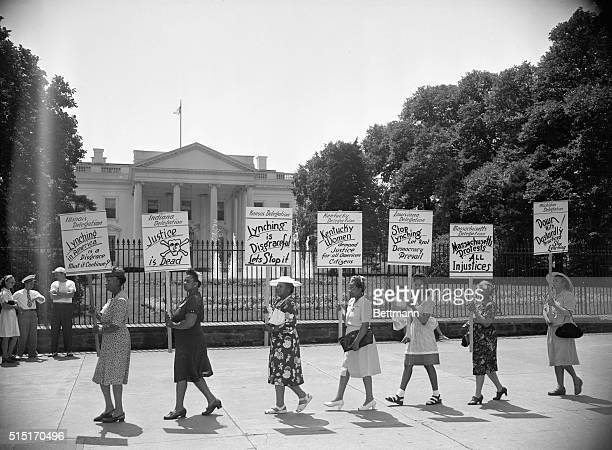 Negro delegates from several states parade with signs in front of the White House to protest the mob slaying of four negroes in Georgia recently The...