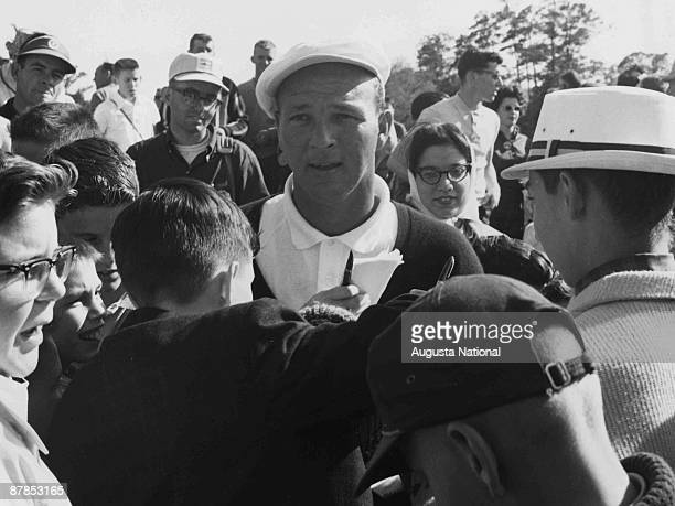 Arnold Palmer signs autographs during a 1960s Masters Tournament at Augusta National Golf Club in Augusta Georgia