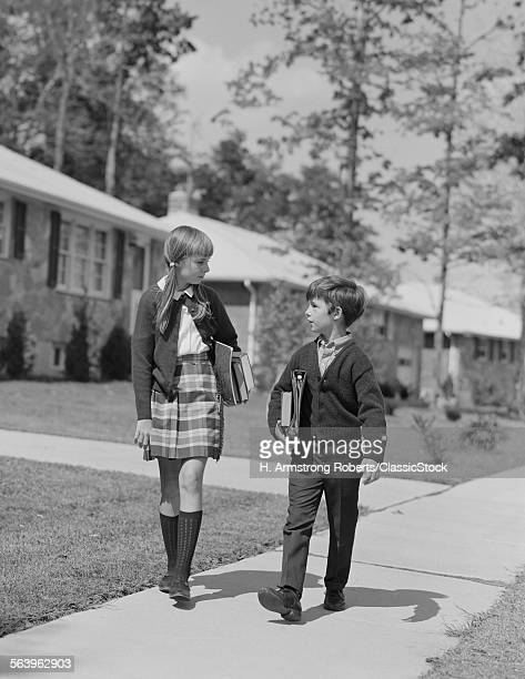 1960s BOY GIRL CARRYING...