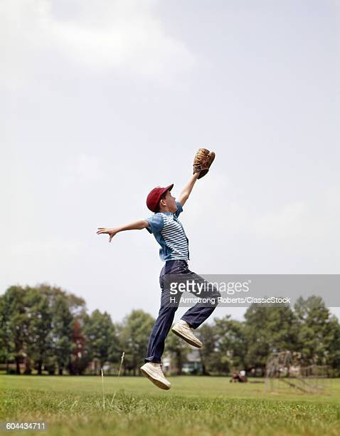 1960s BOY JUMPING TO CATCH.