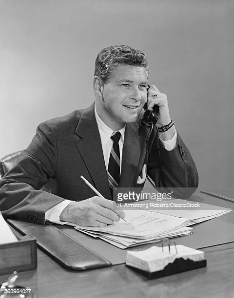 1960s BUSINESSMAN SEATED...