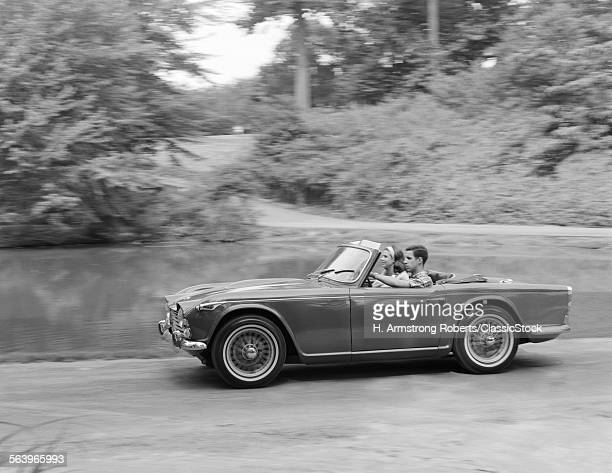 1960s COUPLE DRIVING IN...