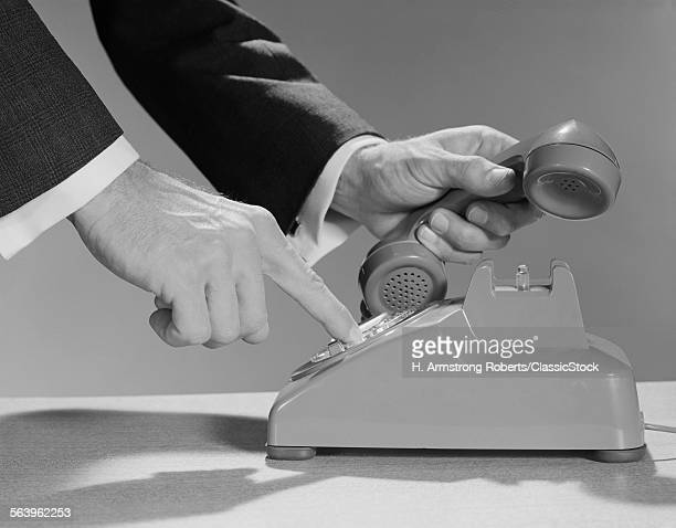 1960s MALE HANDS DIALING...
