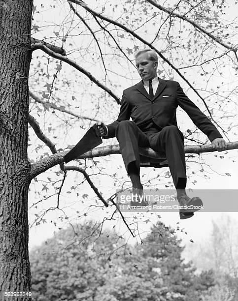 1960s MAN IN TREE BRANCH LIMB