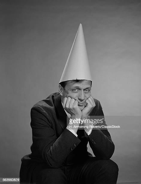 1960s MAN WEARING DUNCE CAP