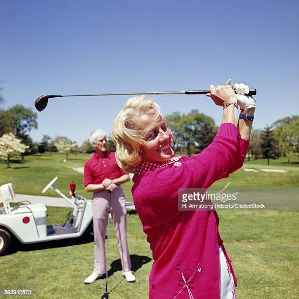 1960s MATURE WOMAN GOLFING...