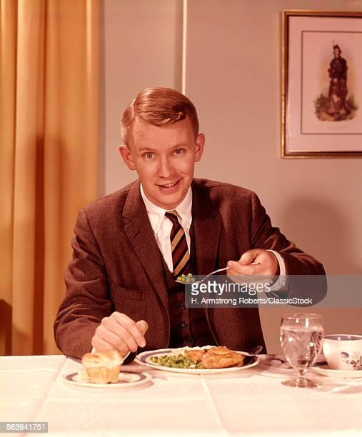 1960s SMILING MAN EATING...