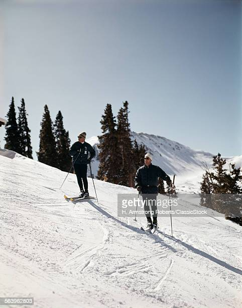 1960s TWO MEN SKIERS ON...