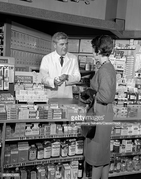 1960s WOMAN AT PHARMACY...