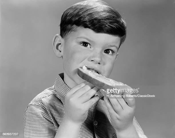 1960s YOUNG BOY EATING...