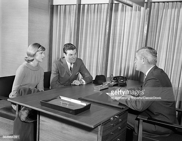 1960s YOUNG COUPLE AT DESK...