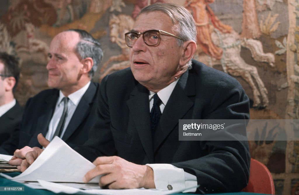 Closeup of French writer-philosopher <a gi-track='captionPersonalityLinkClicked' href=/galleries/search?phrase=Jean-Paul+Sartre&family=editorial&specificpeople=220329 ng-click='$event.stopPropagation()'>Jean-Paul Sartre</a>, seated at table with unidentifed men.