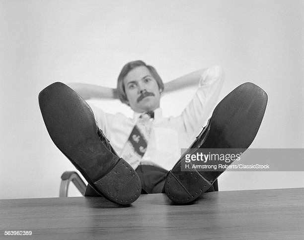 1970s BUSINESSMAN SITTING...